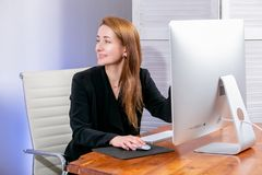 Portrait of happy young successful businesswoman at office. She sits at the table and shows her hand at the display, office work. royalty free stock photography