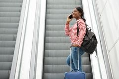 Happy young travel woman talking with mobile phone on escalator stock images