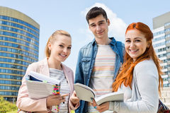 Portrait of happy young university students studying outdoors Stock Images