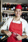 Portrait of a happy young waiter with bottle and glass Stock Images
