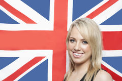 Portrait of happy young woman against British flag Royalty Free Stock Photography