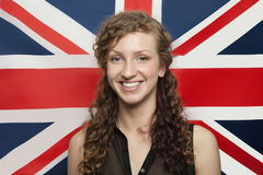 Portrait of happy young woman against British flag Royalty Free Stock Image