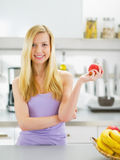 Portrait of happy young woman with apple Stock Photos