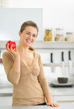 Portrait of happy young woman apple in kitchen Stock Photos