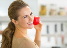 Portrait of happy young woman apple in kitchen Stock Photography