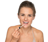 Portrait of happy young woman applying lip gloss Stock Image