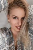 Portrait of a happy young woman with a beautiful smile with blue eyes with sexy lips with blond hair in a fashionable shirt