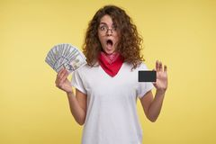 A portrait of happy young woman with brunette curly hair, holding cash and credit cart in the hands, isolated over royalty free stock photography