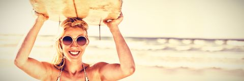 Portrait of happy woman carrying surfboard at beach. Portrait of happy young woman carrying surfboard at beach during sunny day royalty free stock images