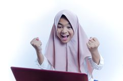 Portrait of happy young woman celebrating success with arms up and shout out in front of laptop royalty free stock images