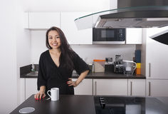 Portrait of happy young woman with coffee mug in kitchen Royalty Free Stock Images