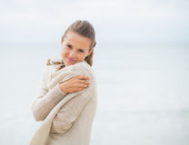 Portrait of happy young woman on cold beach Stock Photos