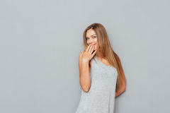 Portrait of a happy young woman covering her mouth. Isolated on a gray background Royalty Free Stock Images