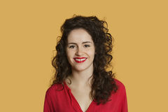Portrait of a happy young woman with curly hair over colored background Stock Photo