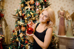 Portrait of happy woman decorating Christmas tree. Portrait of happy young woman decorating Christmas tree Royalty Free Stock Images