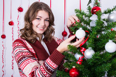 Portrait of happy young woman decorating Christmas tree Stock Photo
