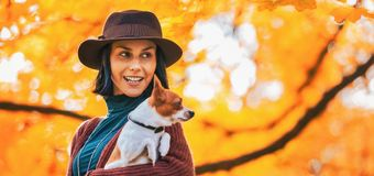 Portrait of happy young woman with dog outdoors in autumn Stock Photo