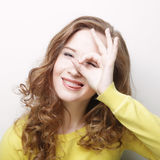Portrait of a happy young woman doing okay sign against white ba Stock Photography
