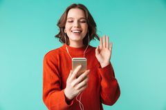 Portrait of a happy young woman dressed in sweater. In earphones talking on mobile phone isolated over blue background Royalty Free Stock Photography