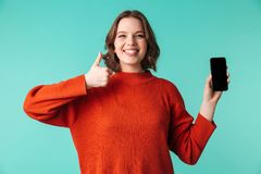 Portrait of a happy young woman dressed in sweater. Holding blank screen mobile phone and showing thumbs up isolated over blue background Royalty Free Stock Photos