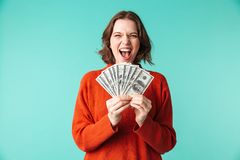 Portrait of a happy young woman dressed in sweater. Holding money banknnotes and screaming isolated over blue background Stock Photos
