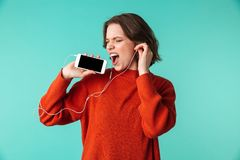 Portrait of a happy young woman dressed in sweater. Listening to music in earphones isolated over blue background Stock Photos