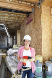 Portrait of a happy young woman with drill at construction site Royalty Free Stock Photo