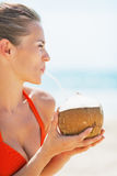 Portrait of happy young woman drinking coconut milk on beach royalty free stock photography
