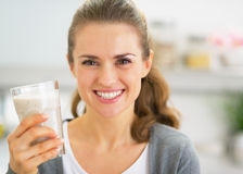 Portrait of happy young woman drinking smoothie in kitchen stock images