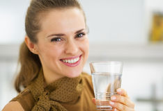 Portrait of happy young woman drinking water in kitchen Royalty Free Stock Images