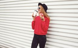 Portrait happy young woman drinks coffee and holding sweet donut on city street white wall. Background royalty free stock photography