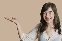 Portrait of a happy young woman with empty hand over colored background Royalty Free Stock Photography