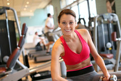 Portrait of a happy young woman in a fitness club excercising Stock Photography