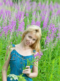 Portrait of the happy young woman among flowers Royalty Free Stock Photography