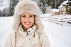 Portrait of happy young woman in furry hat in winter outdoors Royalty Free Stock Image