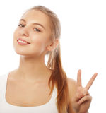 Portrait of happy young woman giving peace sign Stock Photos