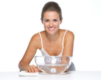 Portrait of happy young woman with glass bowl with water Stock Photo