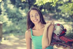 Portrait happy young woman going rollerblading holding in line skates Stock Photo
