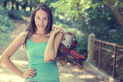 Portrait happy young woman going rollerblading holding in line skates Royalty Free Stock Images
