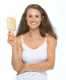 Portrait of happy young woman with hairbrush Royalty Free Stock Photos