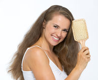 Portrait of happy young woman with hairbrush Royalty Free Stock Images