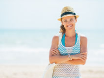 Portrait of happy young woman in hat and with bag on beach Stock Image