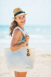 Portrait of happy young woman in hat and with bag on beach Stock Photos