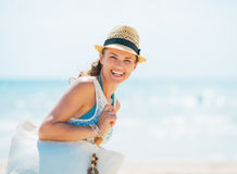 Portrait of happy young woman in hat and with bag on beach Royalty Free Stock Photography