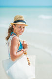 Portrait of happy young woman with hat and bag at seaside Stock Photo