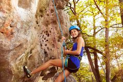 Happy woman rock climbing in forest area. Portrait of happy young woman in helmet rock climbing in forest area royalty free stock photos