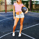 Portrait happy young woman holding basket ball - close up Royalty Free Stock Image