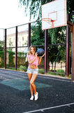 Portrait happy young woman holding basketball on outdoor court Royalty Free Stock Image