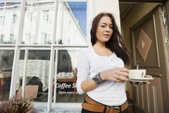 Portrait of happy young woman holding coffee cup in front of cafe Royalty Free Stock Photo