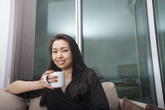 Portrait of happy young woman holding coffee mug in living room Stock Photo